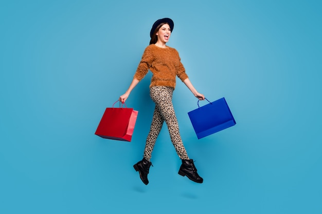 Full length photo of cheerful funky girl enjoy autumn spring holiday shopping  hold beautiful bags go jump walk wear brown pullover retro trousers headwear cap isolated blue color wall