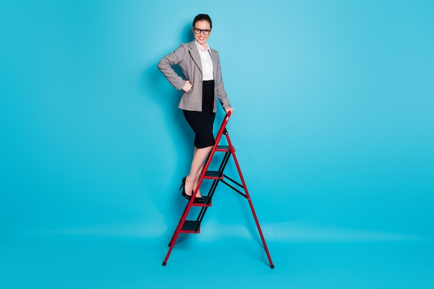 전체 길이 사진 자신감 있는 보스 레이디 등반 경력 사다리 착용 재킷 블레이저 스커트 고립 된 파란색 배경