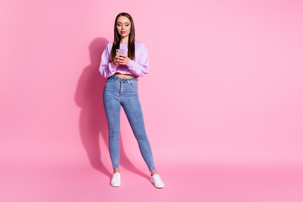 Full length photo of cool addicted blogger girl use smartphone texting typing subscribe  social network news isolated over pastel color background