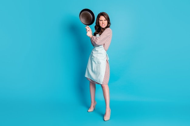 Full length photo of crazy angry mad lady hold hands kitchen utensil frying pan cooking dinner fight boyfriend beating him wear apron dotted dress stilettos isolated blue color background