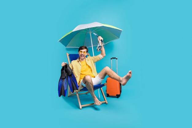 Фото в полный рост сумасшедший парень сидит в шезлонге зонтик отдыхает расслабиться плавать на дне кораллового рифа удерживать ласты очки багаж багаж сумка носить желто-белую рубашку шорты изолированный синий цвет фона