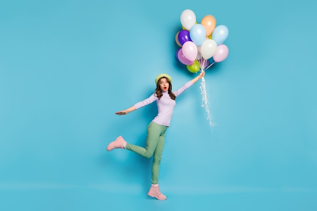 Full length photo of crazy pretty lady hold many air balloons shocked raising up with wind wear purple pullover beret cap green trousers boots isolated blue color wall