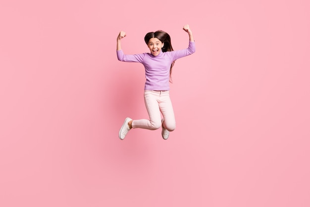 Full length photo of crazy small kid girl jump show triceps hands wear purple sweater trousers isolated over pink color background