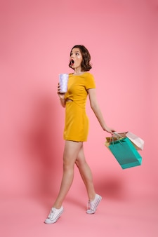 Full length photo of cute amazed woman in yellow dress holding drink and colorful shopping bags, looking aside