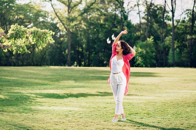 Full-length photo of cute brunette girl walking in summer park. she wears white clothes,  long pink shirt. she is enjoying.
