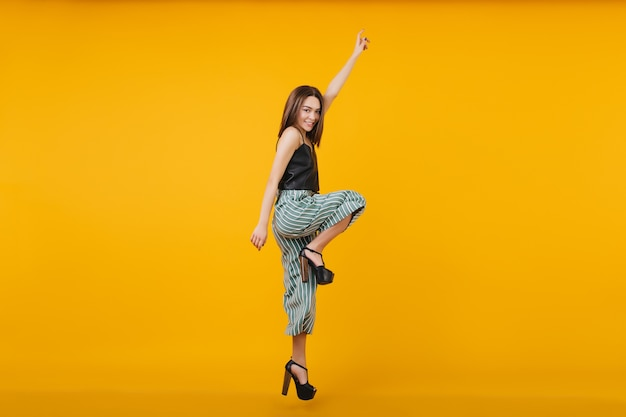 Full-length photo of dancing brunette woman wears high heel shoes. portrait of lovely girl jumping.