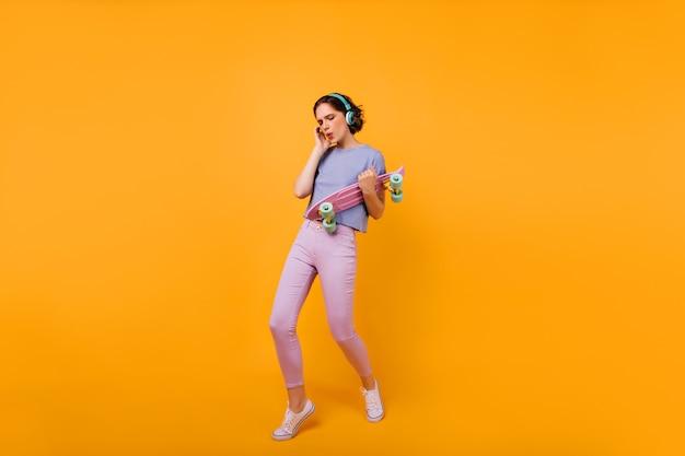 Foto a figura intera di una donna affascinante che balla con il longboard. ritratto di incredibile donna caucasica in posa in cuffia e ascolto di musica.