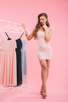 Full length photo of doubting young woman 20s thinking and choosing dresses on clothing rack, isolated over pink wall