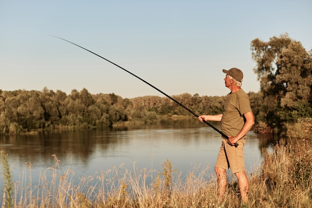 Full length photo of elderly man wearing casual attire and hat holding fishing rod in hands, looking at bobber, enjoying rest and silence.