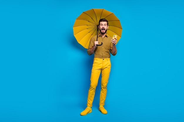 Полная длина фото энергичный парень использует смартфон получить комментарий впечатлен крик омг удерживайте защиту от дождя щит зонтик носить стиль стильные модные клетчатые брюки изолированы синего цвета