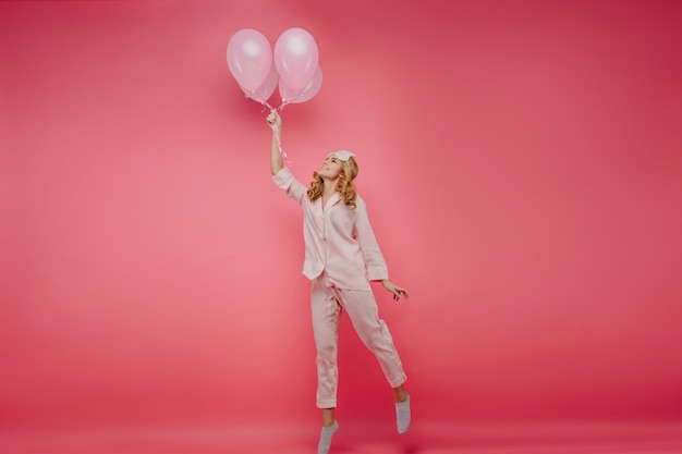 Full-length photo of enthusiastic blonde girl posing with balloons. indoor portrait of cheerful lady in sleepmask standing on tip-toe in her birthday.