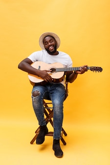 Full-length photo of excited artistic man playing his guitar. isolated on yellow background.