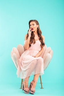 Full length photo of excited woman 20s in pink dress sitting in soft armchair with legs crossed and open mouth, isolated over blue wall