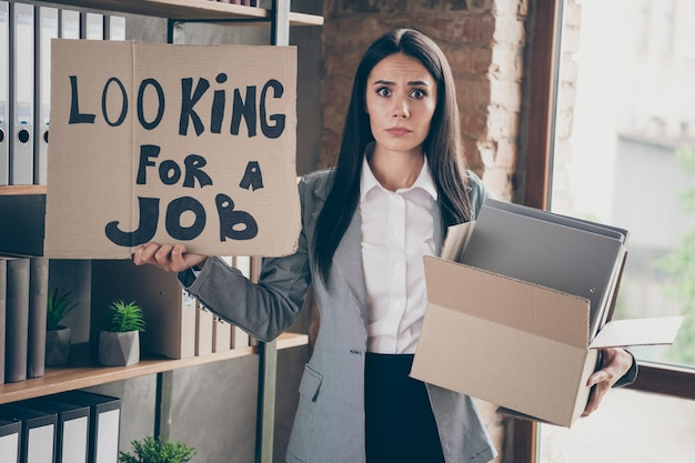 Full length photo of frustrated girl feel despair lose company bankrupt crisis hold cardboard text look for job box with folders wear blazer jacket suit in workstation