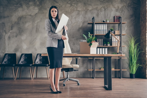 Full length photo of frustrated stressed girl agent marketer dont want quit job office hold computer pc screen wear blazer jacket high-heels in workplace workstation
