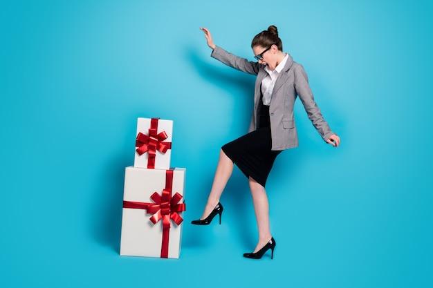 Полная длина фото весело девушка имеет стек подарок танцевальная одежда юбка пиджак пиджак на высоких каблуках изолированный синий цвет фона