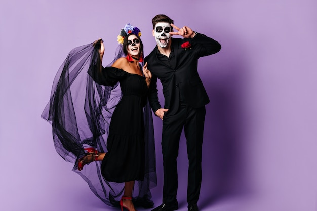 Full-length photo of funny guy and girl in masquerade masks laughing and posing in good mood. lady in black veil with flowers in her hair touches boyfriend showing peace sign.
