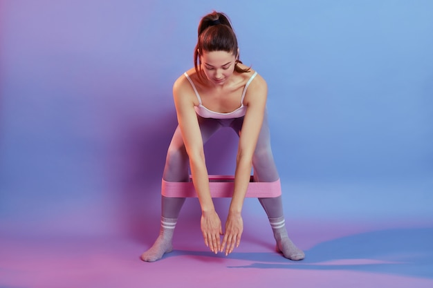 Full-length photo of girl in sportswear using resistance band in her legs, leans her body down on color background, female squats, looks down, workout indoor.