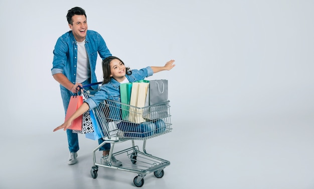 Full-length photo of happy attractive man in a casual outfit, riding a shopping cart with his smiling daughter, who is imitating a plane, and three shopping bags in it.