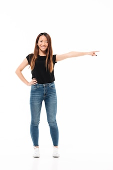 Full length photo of happy charming asian woman in casual wear standing with outstretched hand, pointing with finger, looking at camera