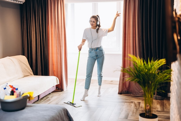 Full length photo of happy cheerful woman is washing floor in room with mop having fun