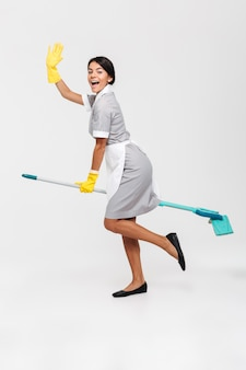 Full length photo of happy funny girl in uniform riding mop as a witch