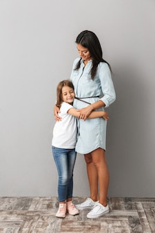 Full length photo of happy woman with little girl smiling and hugging together, isolated over gray