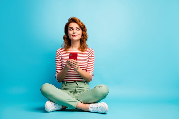Full length photo of inspired dreamy woman sit floor legs crossed look copyspace use smartphone think want type blog post wear white stylish clothing shoes isolated blue color