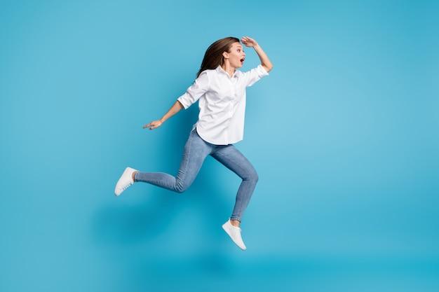 Полная длина фото леди прыжок высоко бегает взгляд далеко заинтересованный носить белую рубашку джинсовую обувь изолированный синий цвет фона