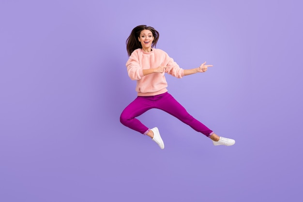 Full length photo of lady jumping high indicating fingers empty space on purple wall