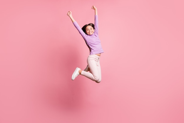 Full length photo of little kid girl jump raise hands wear violet sweater isolated over pastel color background