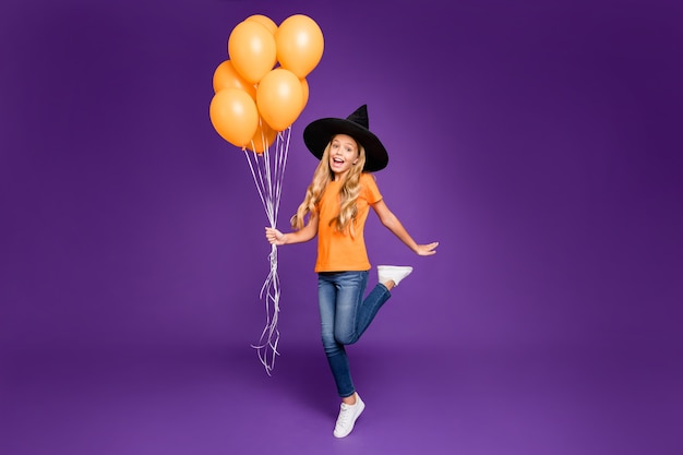 Full length photo of little witch lady halloween party holding many air balloons excited chilling wear orange t-shirt wizard hat isolated purple color background