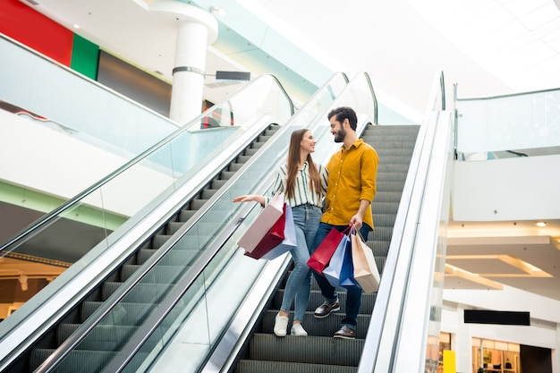 Full length photo of  lovely lady handsome guy talking couple spend free time carry many bags moving down escalator shopping mall hug wear casual jeans shirt footwear outfit indoors