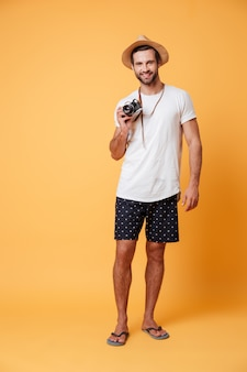 Full-length photo of man with retro camera in hands