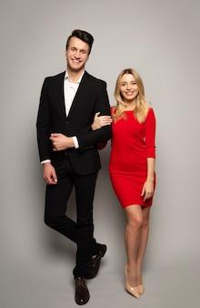 Фотография в полный рост красивой блондинки в красном платье и высокого красивого мужчины в черном костюме, которые позируют впереди, оба смотрят в камеру с большими улыбками.