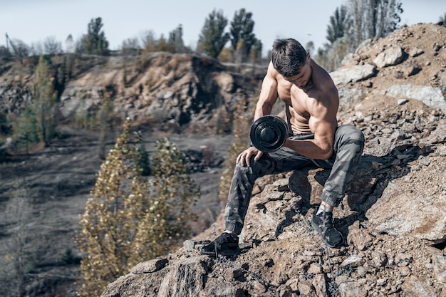 金属製のダンベルを手にしたボディービルダーの全身写真。上半身裸のボディービルダー。背景の岩。
