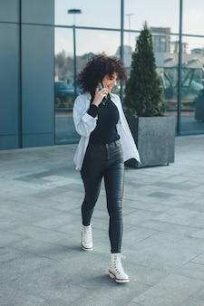 Полная длина фото кавказской женщины с вьющимися волосами, говорящей по телефону на улице и улыбающейся