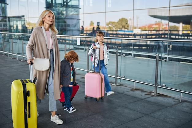 Фотография в полный рост женщины, идущей с двумя детьми с багажом по стеклянной ограде в аэропорт