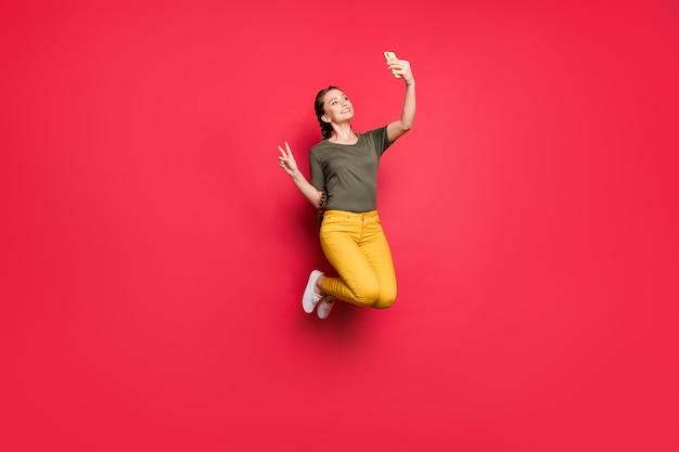 Vサインのシンボルを示すセルフィーを高くジャンプするアクティブな女性の全身写真陽気な気分はカジュアルな黄色のズボン緑のtシャツ孤立した赤い色の背景を着用します