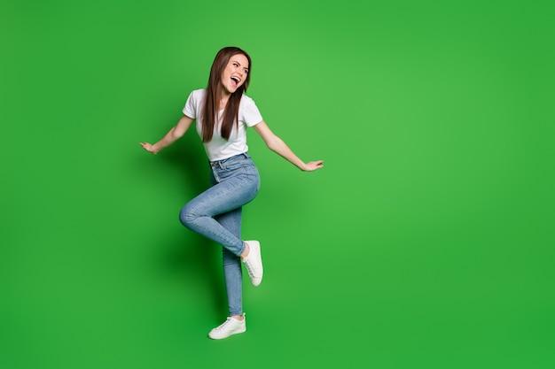 緑の背景に分離された愛らしい夢のような若い女性のダンスウェアジーンズtシャツ靴の完全な長さの写真