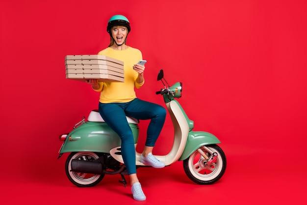 Полная длина фото изумленной девушки, сидящей на велосипеде, с телефоном, коробки для пиццы, принимающей заказ