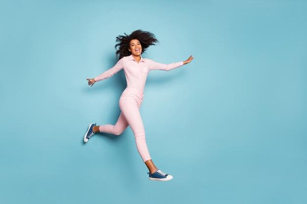 놀라운 어두운 피부 아가씨 점프 높은 확산 손의 전체 길이 사진 외부 착용 최고의 자유 시간을 보내는 측면 핑크 셔츠 바지 절연 파란색 배경