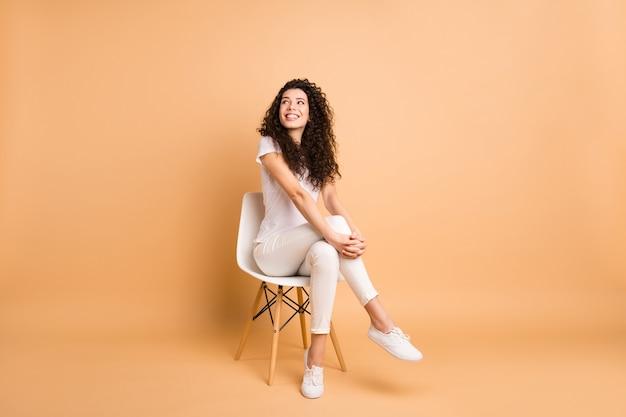 快適な椅子に座って興味を持って空のスペースを探している素晴らしい女性の全身写真良い気分に触発されたカジュアルな服を着る孤立したベージュのパステルカラーの背景