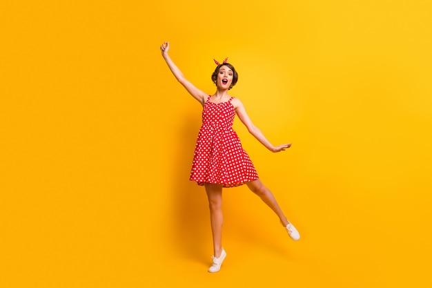 Полная фотография изумленной симпатичной красивой девушки, держащей руку, ловит ее летающий зонт в ветреную погоду, воображение, зонтик, крик, одежда в горошек, обувь в горошек, изолированная над блестящей цветной стеной