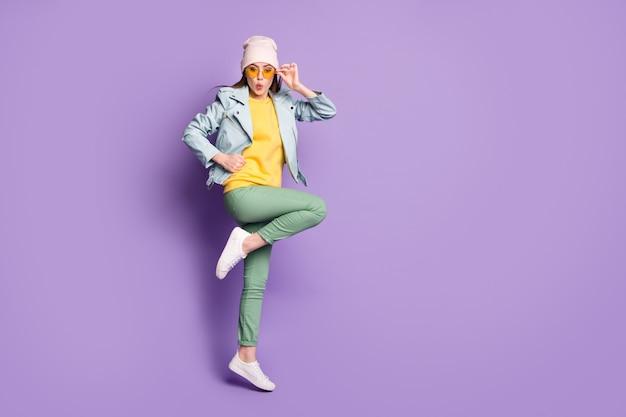 놀란 소녀 점프의 전체 길이 사진은 생생한 색상 배경 위에 격리된 멋진 옷을 입고 믿을 수 없을 정도로 예상치 못한 할인을 받았습니다.