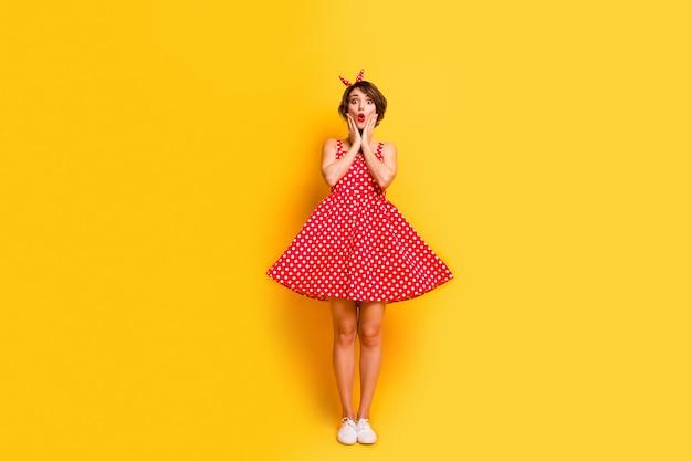 Фото в полный рост изумленной девушки, расслабиться, весенний отдых, выглядеть невероятно, новинка, прикоснуться, руки, лицо, впечатлило, крик, носить стильную одежду в горошек, туфли, изолированные на стене желтого цвета