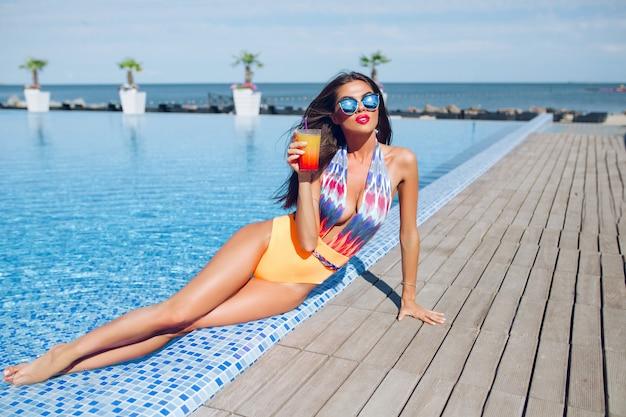 プールのそばに横になっている長い髪を持つ魅力的なブルネットの少女の全身写真。彼女はカラフルな水着とサングラスをかけ、足を水中に保ち、カクテルを持っています。