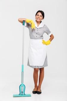 Полная фотография привлекательной брюнетки в униформе, стоящей на швабре, стоя