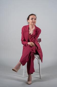 魅力的なシックなビジネス女性の完全な長さの写真座る椅子は赤いスーツハイヒールの孤立した灰色の背景を着用します