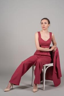 魅力的なシックなビジネスの女性の座る椅子の完全な長さの写真は赤いスーツハイヒールの孤立した灰色の背景